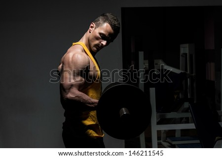 young man doing heavy weight exercise for biceps - stock photo
