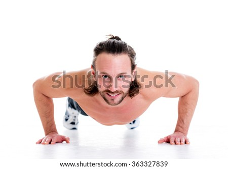 young man doing press-up in front of white background
