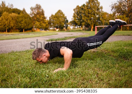 Young man doing push-up outdoor.