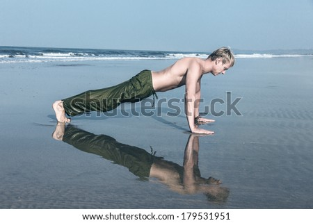 Young man doing push ups during fitness training on sea beach