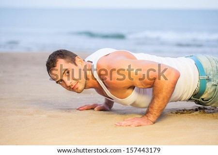 Young man doing push ups on a beach