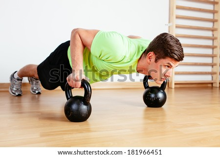 Young man doing push-ups on kettlebell weights