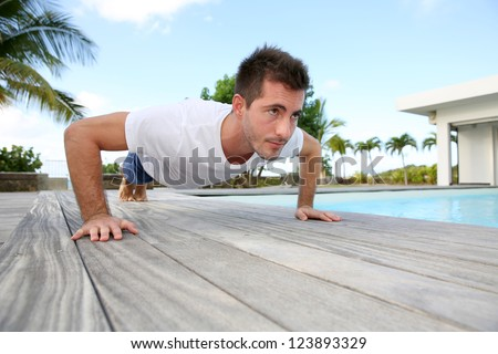 Young man doing pushups on pool deck - stock photo