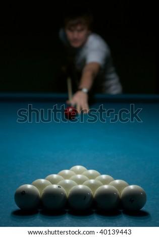 Young man doing shoot on billiard - stock photo