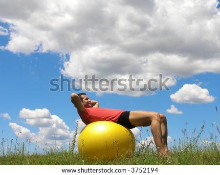 Young man  doing sit-ups on pilates  ball. - stock photo