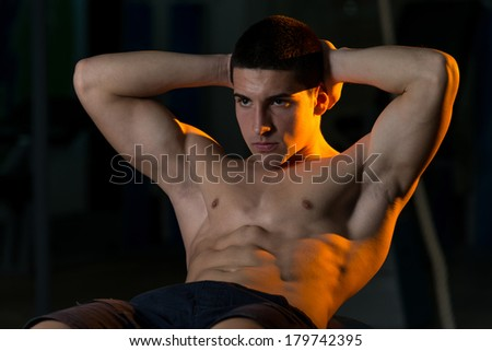 Young Man Doing Sit-Ups With Exercise Ball - stock photo