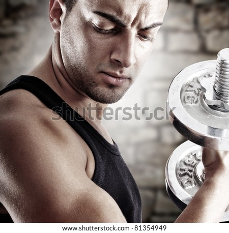 Young man doing weights lifting on stone background - stock photo