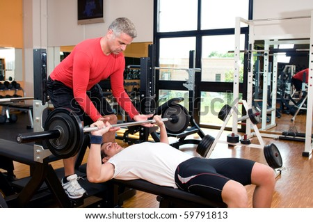 Young man doing weigths on a bench press with the help of the mature instructor at gym - stock photo