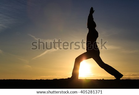 young man doing yoga at sunset sky