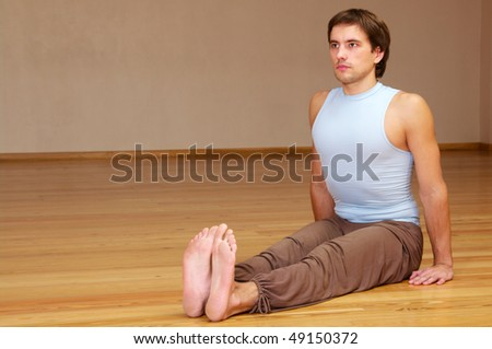young man doing yoga exercise indoor - stock photo
