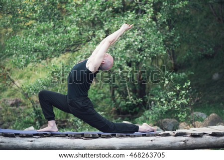 Young man doing yoga exercises in wild untouched nature environment. He meditating on small wooden bridge above cold mountain river. Outdoor photo.