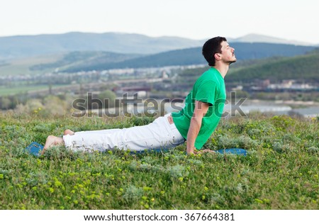 Young man doing yoga fitness exercise outdoor in beautiful mountains landscape. Morning sunrise. Meditation and Relax - stock photo