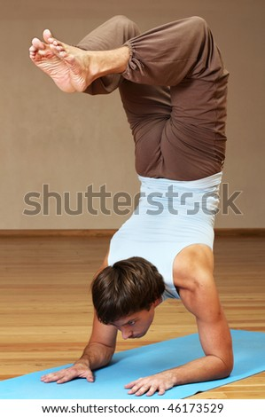young man doing yoga indoor - stock photo