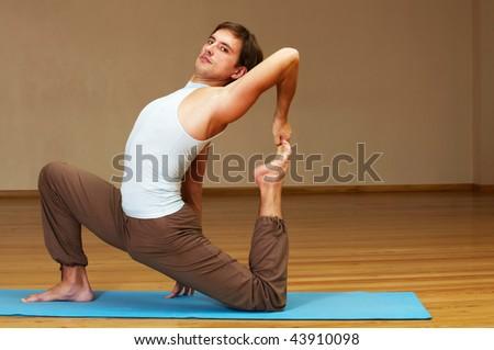 young man doing yoga indoors - stock photo