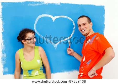 Young man drawing a heart on the wall for his girlfriend