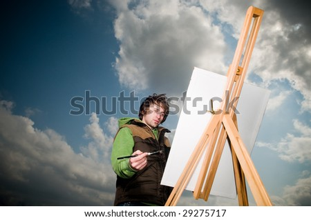 Young man drawing outdoors over dramatic sky background - stock photo
