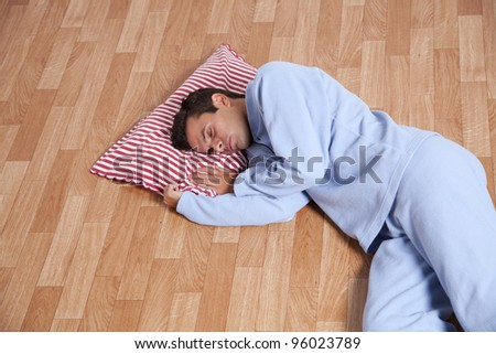 Young man dress with nightclothes sleeping on the floor (isolated on white) - stock photo
