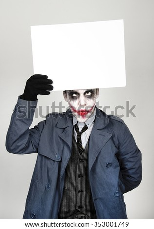 young man dressed as joker showing a blank. crazy gesture