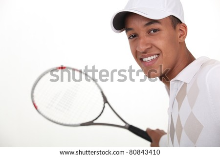 Young man dressed for tennis - stock photo