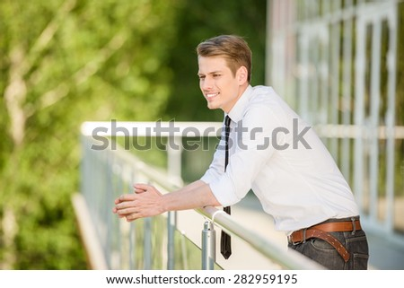 Young man dressed formal resting at office balcony. - stock photo