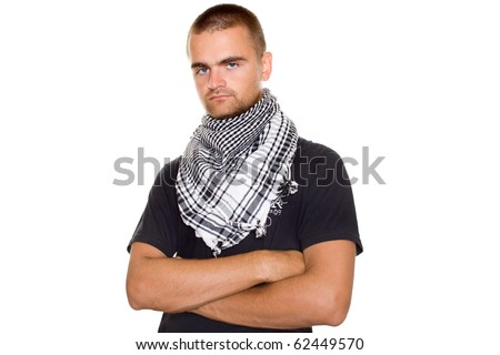 Young man dressed in black t-shirt at the neck of a Palestinian scarf. Hands crossed on his chest. Stubble on his face. Lots of copyspace and room for text on this isolate - stock photo