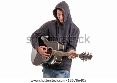 Young man dressed  in hoodie try to understand how to play acoustic guitar, studio shoot. pleased to play an instrument - stock photo