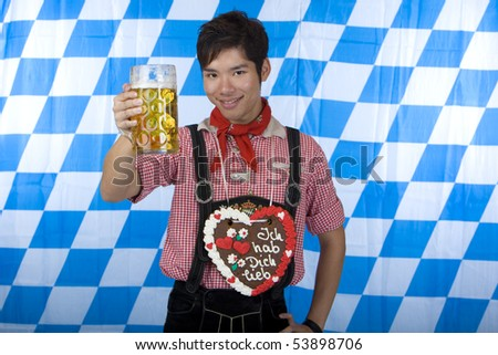 Young man dressed in leather pants (lederhose) holding an Oktoberfest beer stein into camera. In Background is the Bavarian flag visible. - stock photo