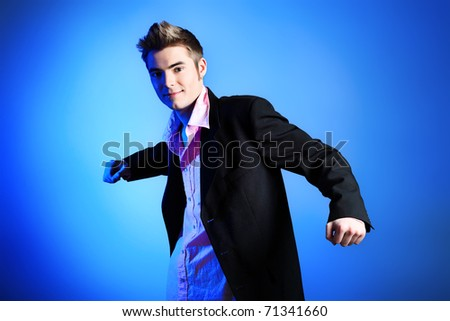 Young man dressed in rock'n'roll style, dancing over blue background.