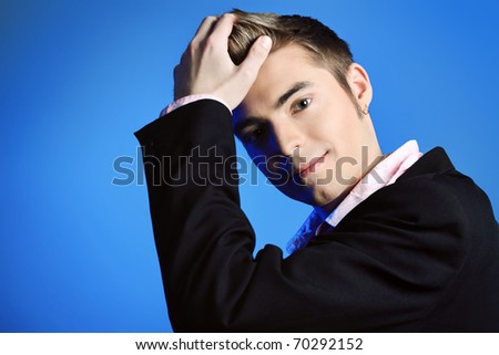 Young man dressed in rock'n'roll style, posing over blue background. - stock photo