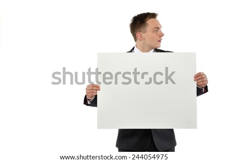 Young man dressed with suit holding white empty paper and looking at right. Isolated on white background.