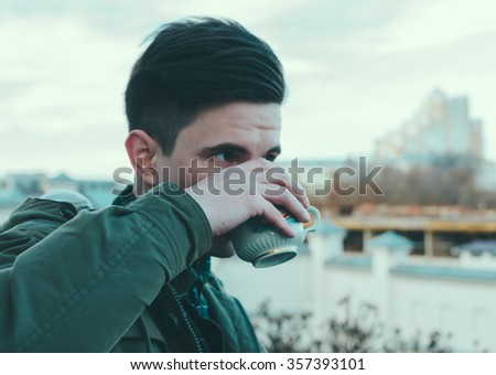 Young man drink a coffee on the city street