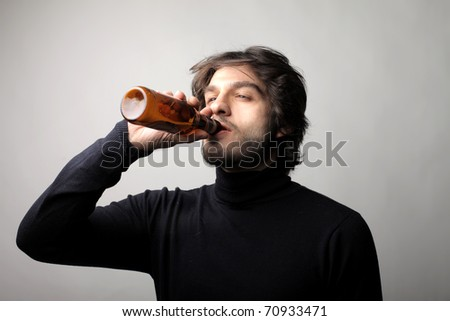 Young man drinking a beer - stock photo