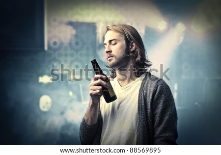 Young man drinking a beer at a party - stock photo