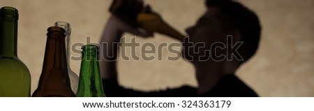 Young man drinking beer during party at home - stock photo