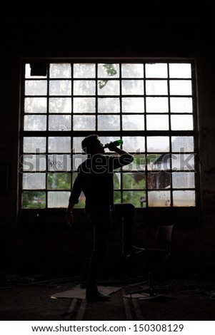 Young man drinking beer in a dark abandoned industrial building - stock photo