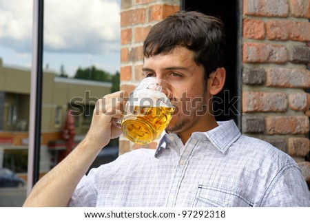 Young man drinking beer in glass bock, could be student or alcoholic. - stock photo