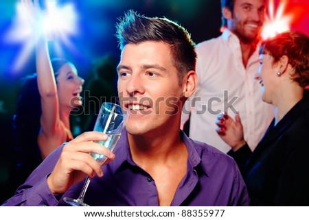 Young man drinking champagne at a party, people dancing at background.? - stock photo