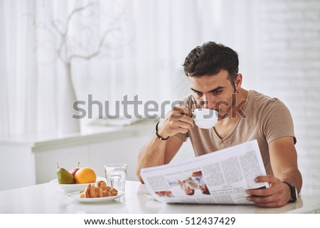 Young man drinking coffee and reading newspaper at home