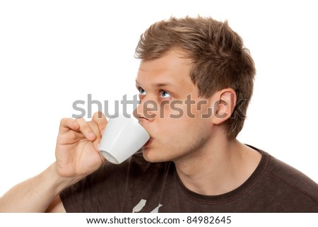 Young man drinking coffee from a coffee cup  looking away isolated on white background - stock photo