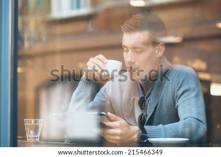 Young man drinking coffee in cafe using tablet computer - stock photo