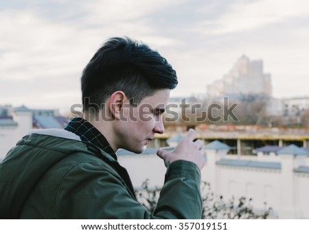 Young man drinking coffee on the city street in autumn time - stock photo