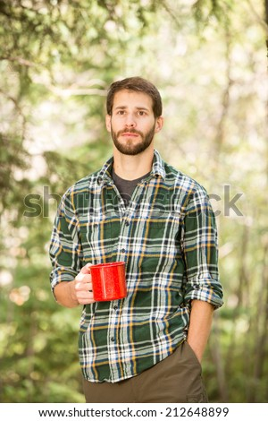 Young Man Drinking Coffee - This is a shot of a young man enjoying a hot cup of coffee outside on a camping trip. - stock photo