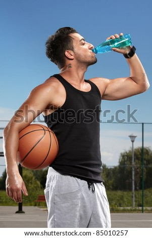 Young man drinking mineral water on a basketball court - stock photo