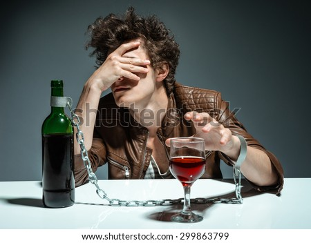 Young man drinking red wine and feeling despair / photo of youth addicted to alcohol, alcoholism concept, social problem - stock photo