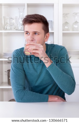young man drinking refreshing lemonade in his modern kitchen - stock photo