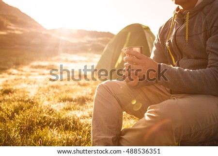 Young man drinking tea at sunrise in mountains.