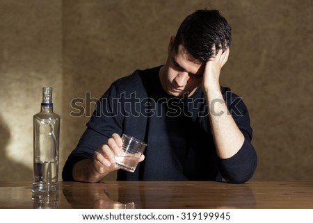 Young man drinking vodka in the glass - stock photo