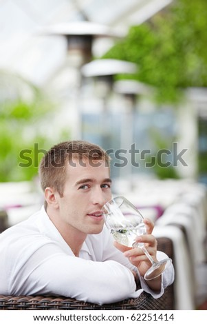 Young man drinking water at a restaurant - stock photo