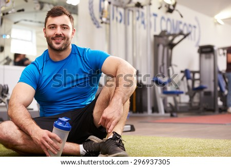 Young man drinking water in a gym - stock photo