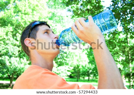 Young man drinking water in heat.